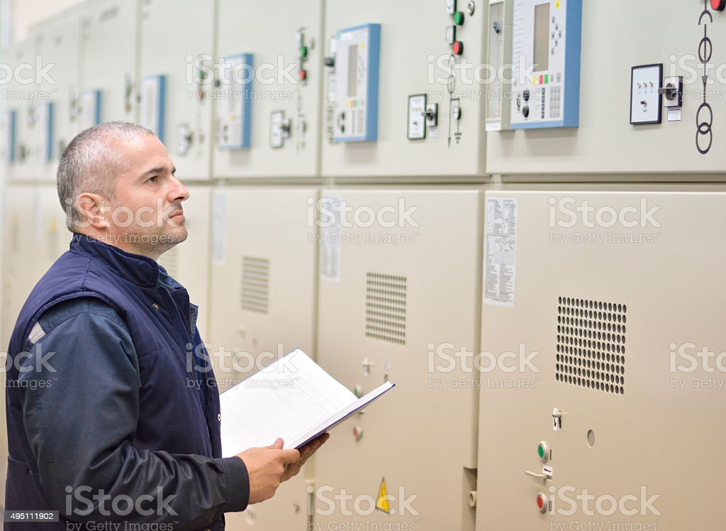 Engineer looks at file on control panel stock photo