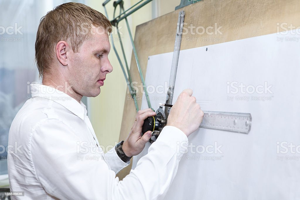 Engineer making construction project by pencil on drawing board royalty-free stock photo