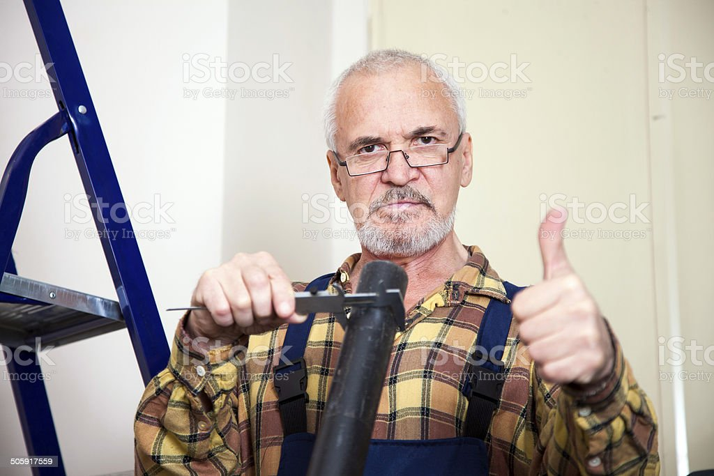Engineer measures with tool the size of the pipe royalty-free stock photo