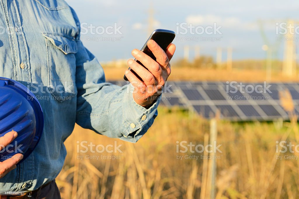 Engineer Messaging in Solar Panel Site royalty-free stock photo