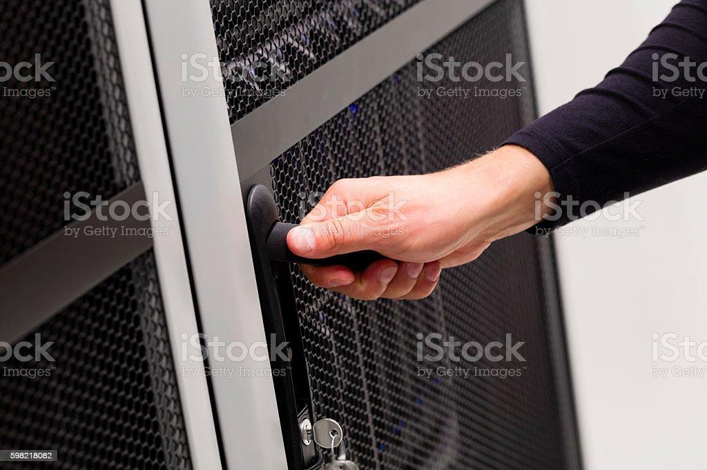 IT engineer opens door to server rack in datacenter stock photo