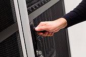 IT engineer opens door to server rack in datacenter
