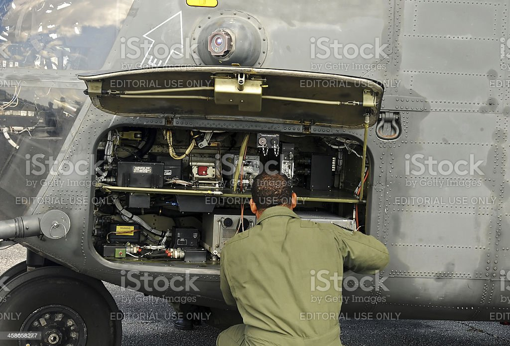 Engineer performs military elicopter maintenance stock photo