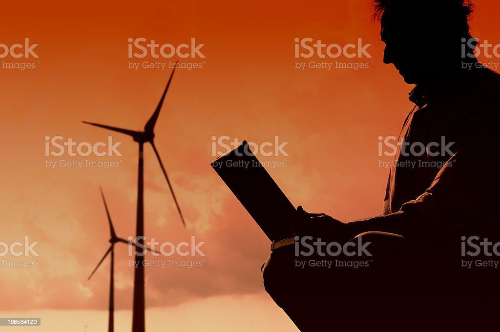Engineer Planning PC in a Wind Turbine Farm at Sunset royalty-free stock photo