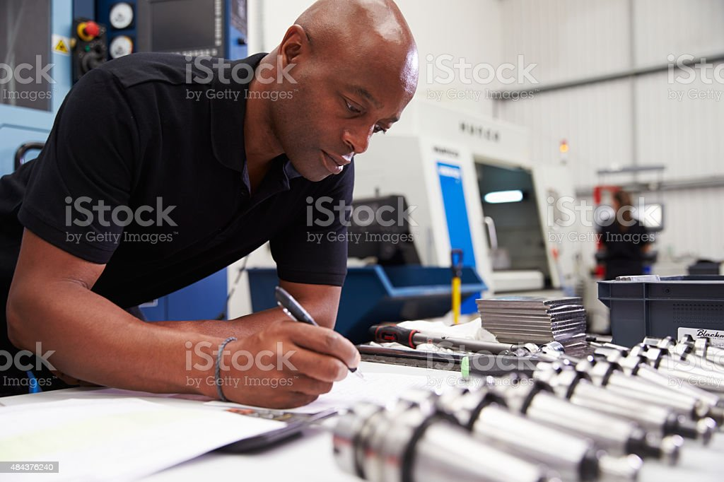Engineer Planning Project With CNC Machinery In Background stock photo