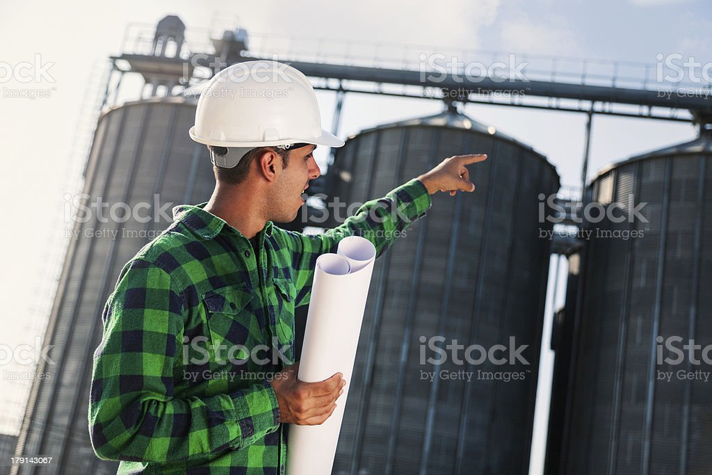 Engineer pointing to silo royalty-free stock photo