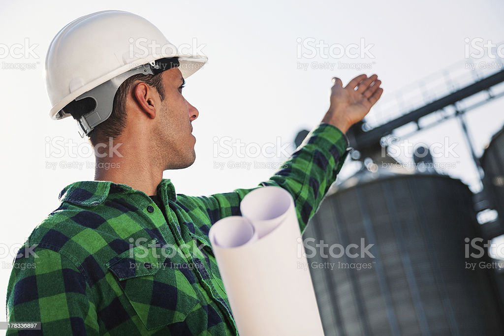Engineer pointing to silo tank royalty-free stock photo