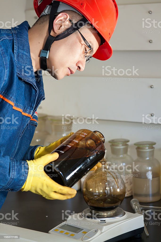 Engineer pouring the oil sample into experimental flask royalty-free stock photo