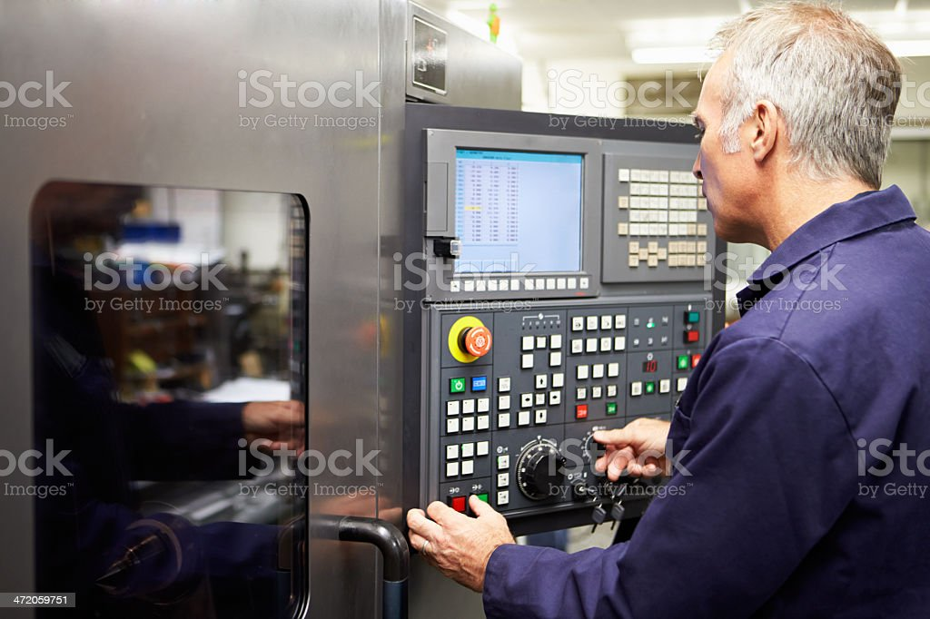 Engineer programming functions of computer controlled Lathe stock photo