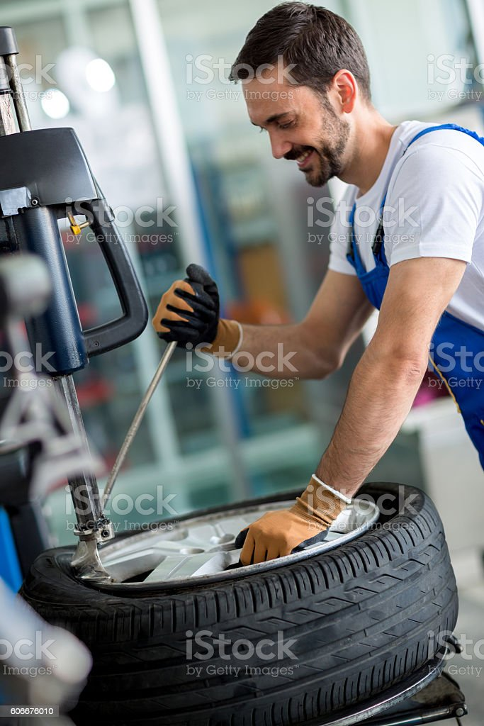Engineer  replace tire on wheel stock photo