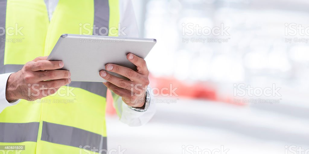 Engineer reviewing plans for construction site on digital tablet stock photo