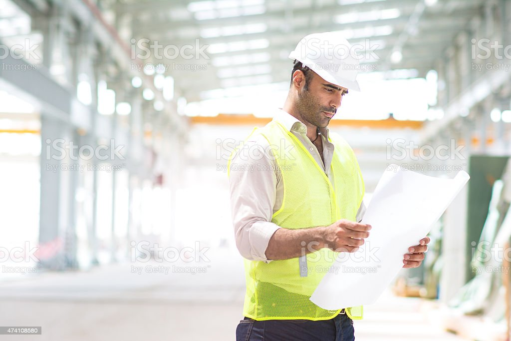 Engineer reviewing plans for construction site. stock photo