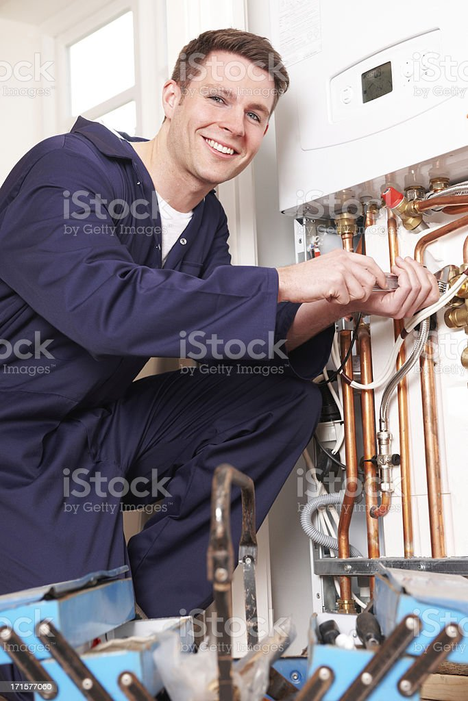 Engineer Servicing Central Heating Boiler stock photo
