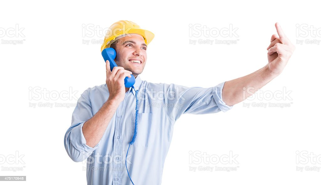 Engineer showing middle finger while talking on the phone stock photo