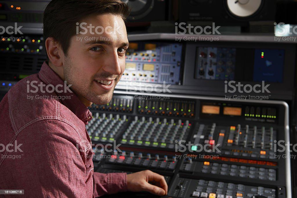 Engineer Sitting At Mixing Desk In Recording Studio stock photo