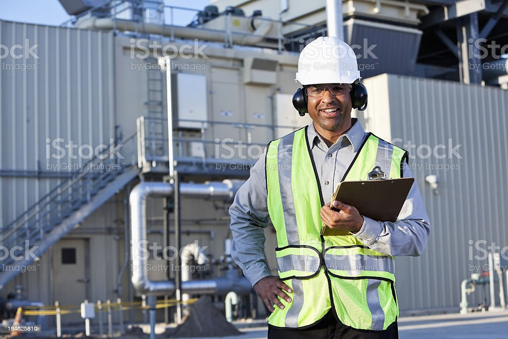 Engineer standing in front of power generator royalty-free stock photo