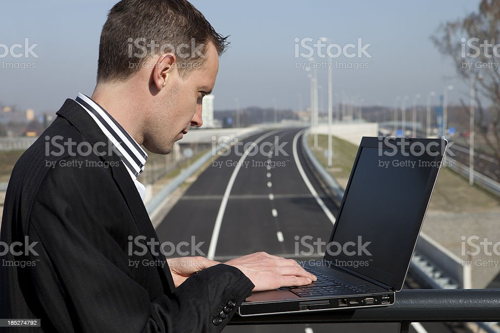 Engineer standing on bridge and looking at laptop royalty-free stock photo