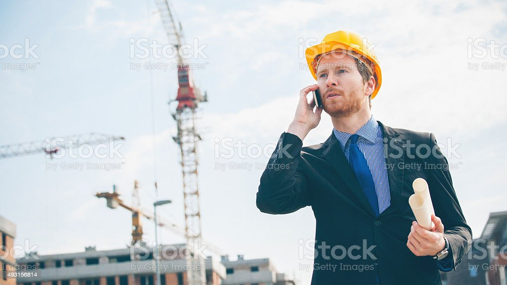 Engineer talking on the smart phone and holding blue prints stock photo