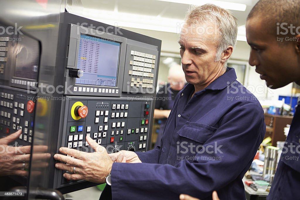 Engineer Teaching Apprentice To Use Computerized Lathe stock photo