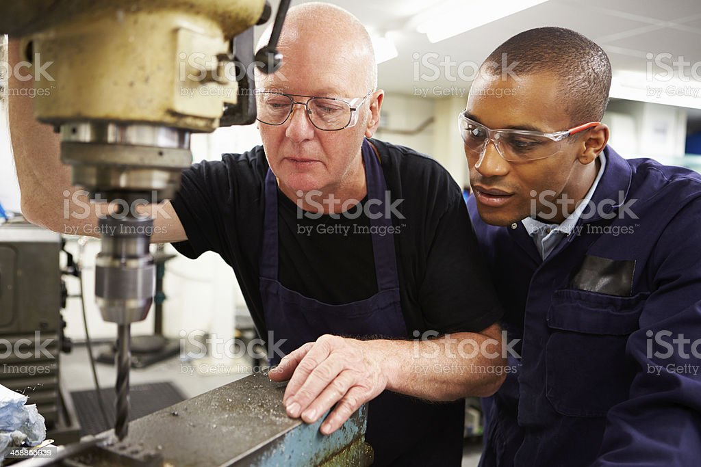 Engineer Teaching Apprentice To Use Milling Machine stock photo