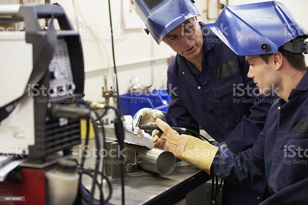 Engineer Teaching Apprentice To Use TIG Welding Machine stock photo