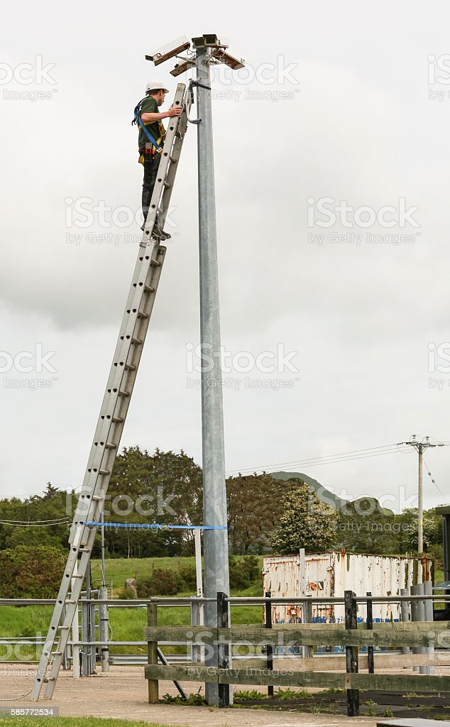 Engineer technician maintaining high level CCTV cameras on a ladder stock photo