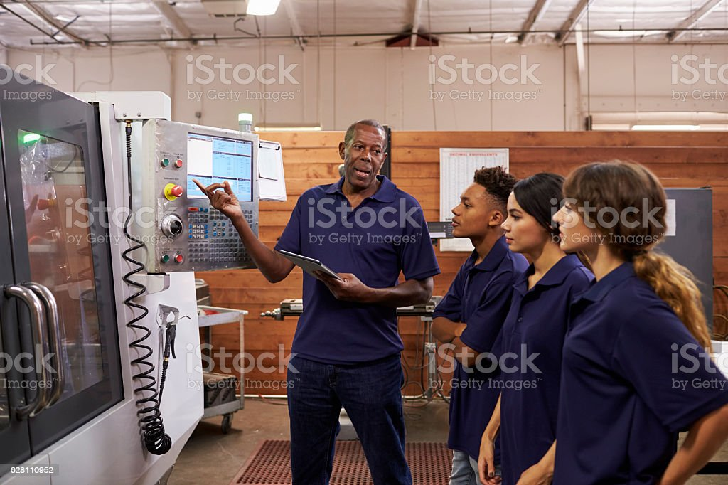 Engineer Training Apprentices On CNC Machine stock photo