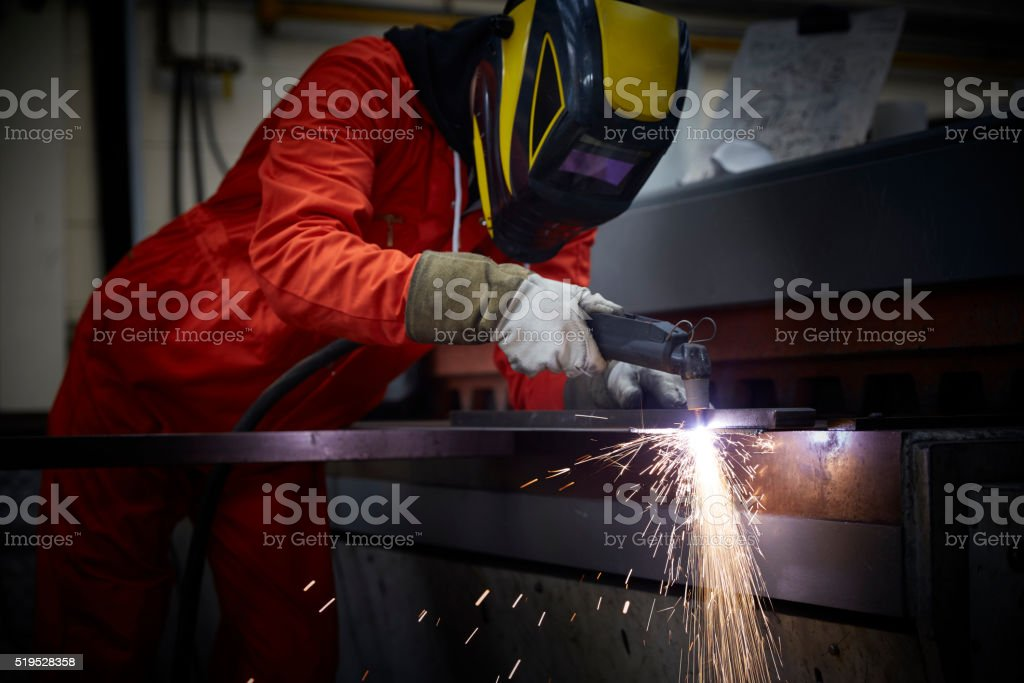 Engineer using plasma cutter in steel fabrication factory stock photo