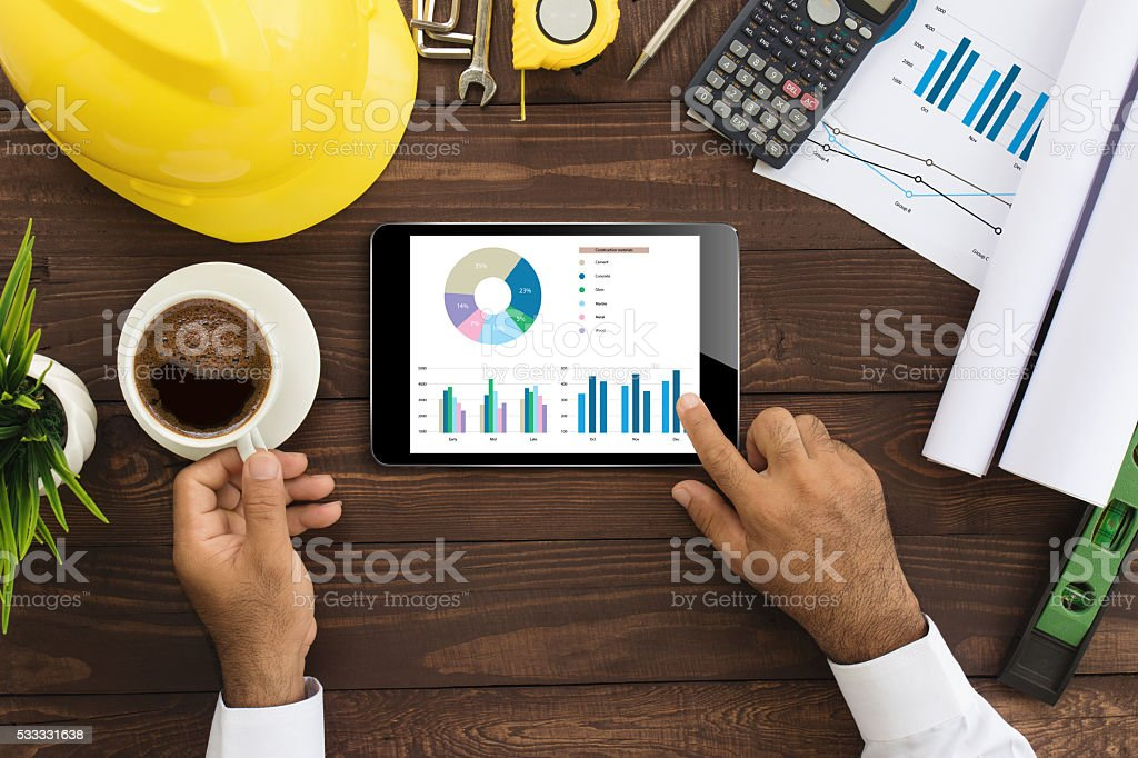 engineer using tablet checking business graph on work table stock photo