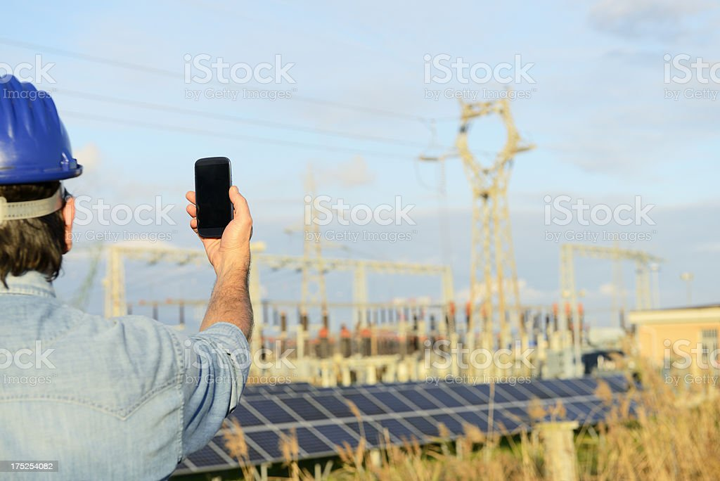 Engineer W Smart Phone in a Solar Power Station royalty-free stock photo
