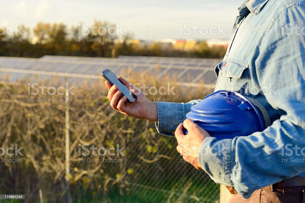 Engineer W Smart Phone in Solar Power Station royalty-free stock photo