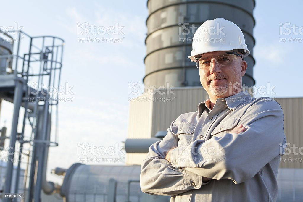 Engineer wearing hardhat at industrial facility stock photo
