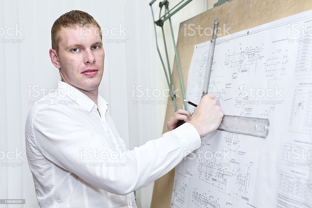Engineer with blueprint standing near old drawing board royalty-free stock photo