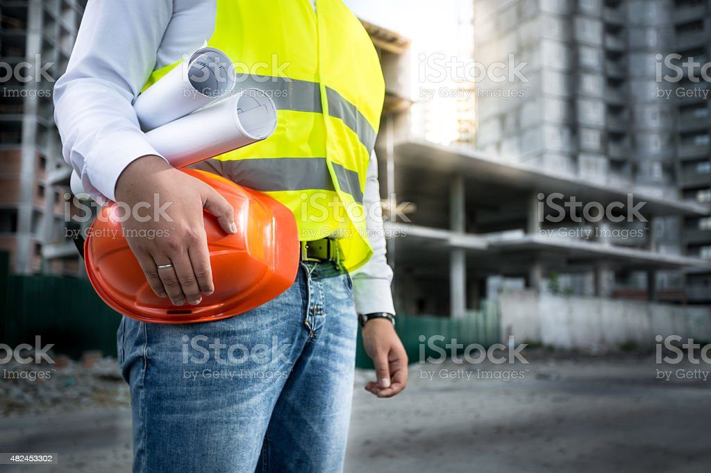 engineer with hardhat and blueprints posing on building site stock photo
