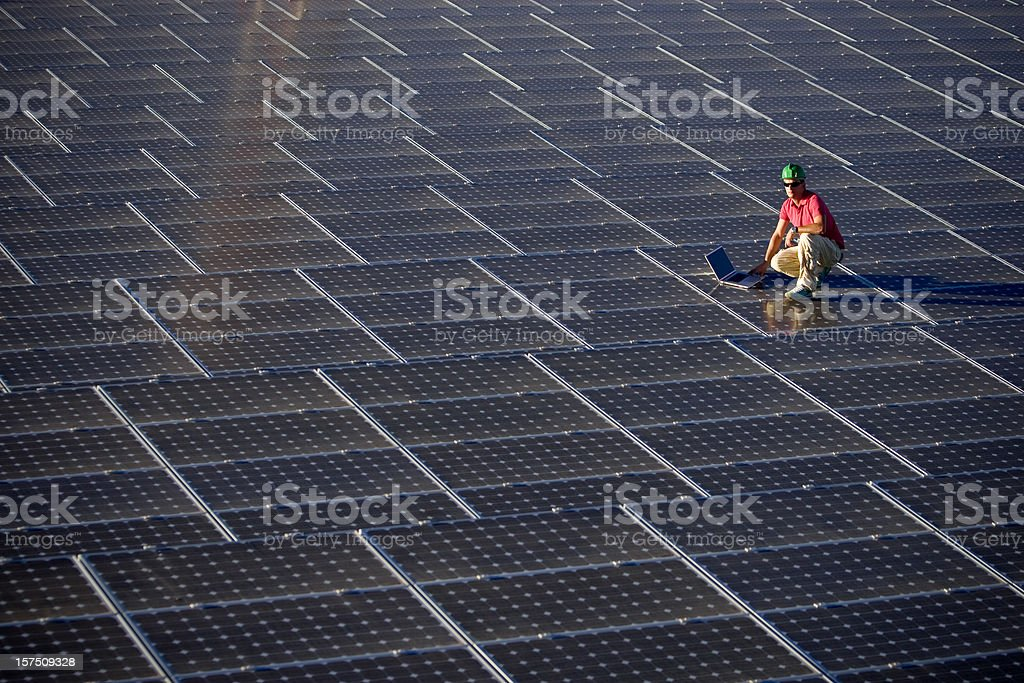 Engineer with laptop working on solar panels royalty-free stock photo