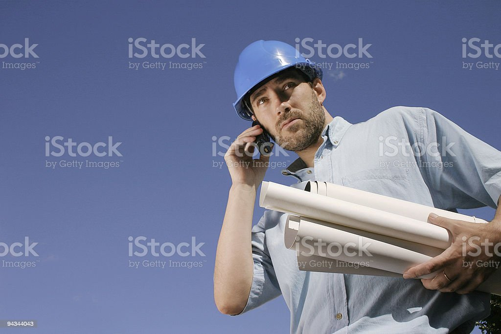 Engineer with phone and blueprints royalty-free stock photo