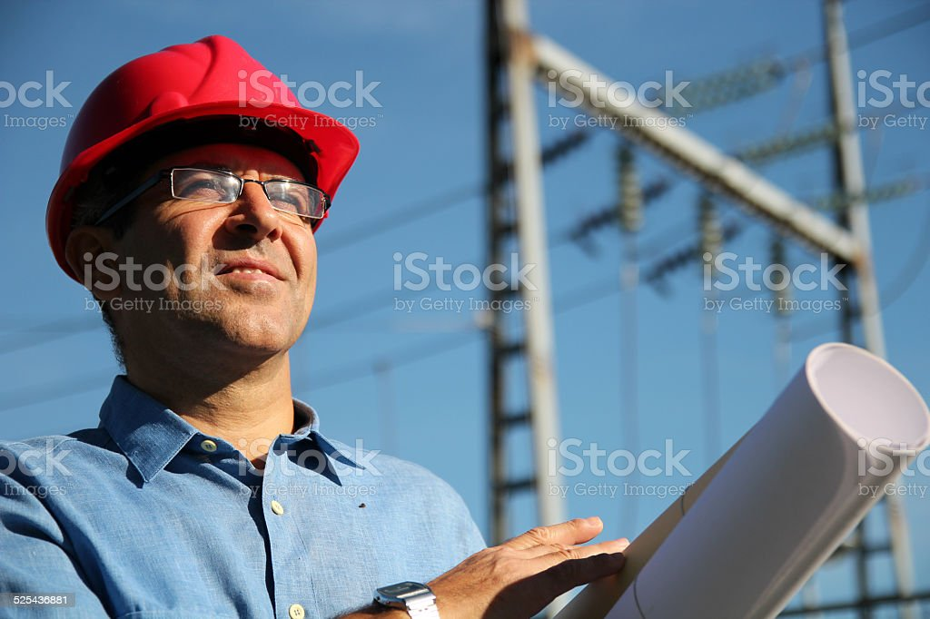 Engineer With Red Hardhat and Blueprint Under the Power Lines stock photo