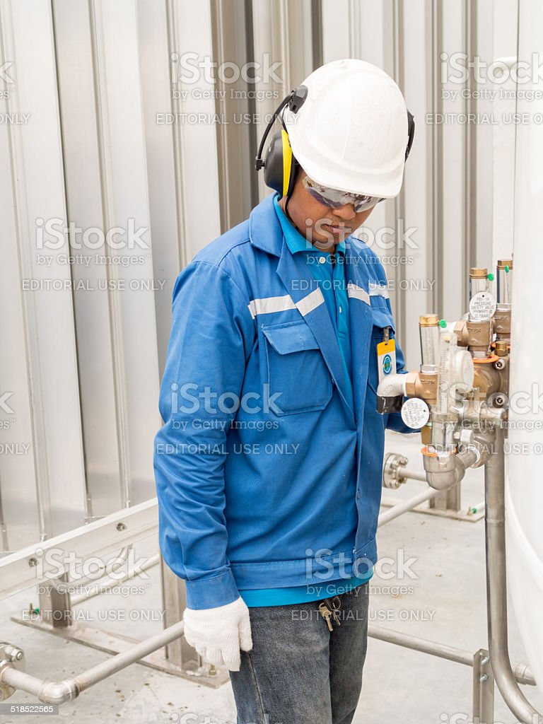 Engineer with safety ear muffs helmet for liquid gas supply stock photo