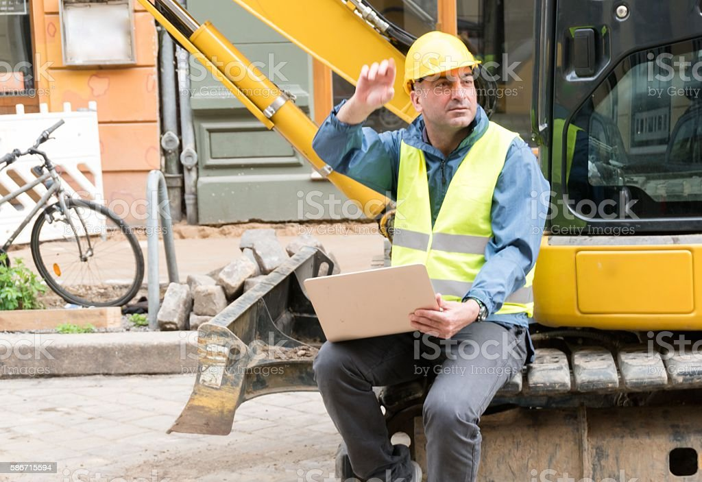Engineer working at computer on construction site stock photo