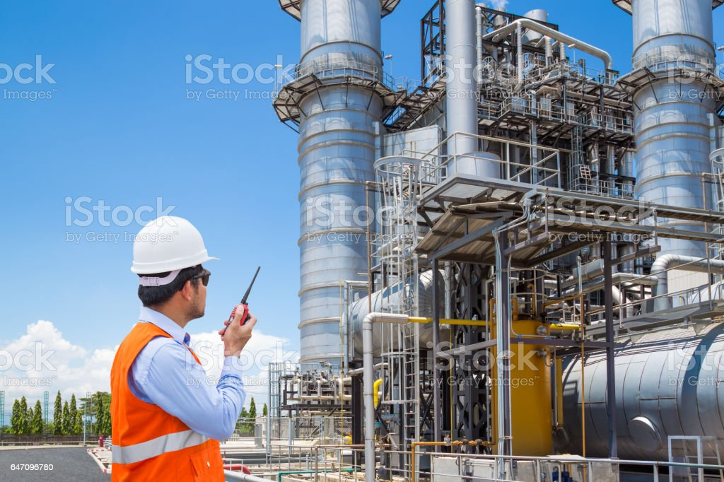 Engineer working at thermal power plant with radio stock photo