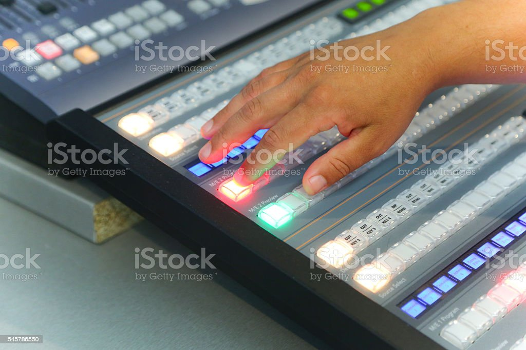 Photo of the TV engineer working editing with video and audio mixer