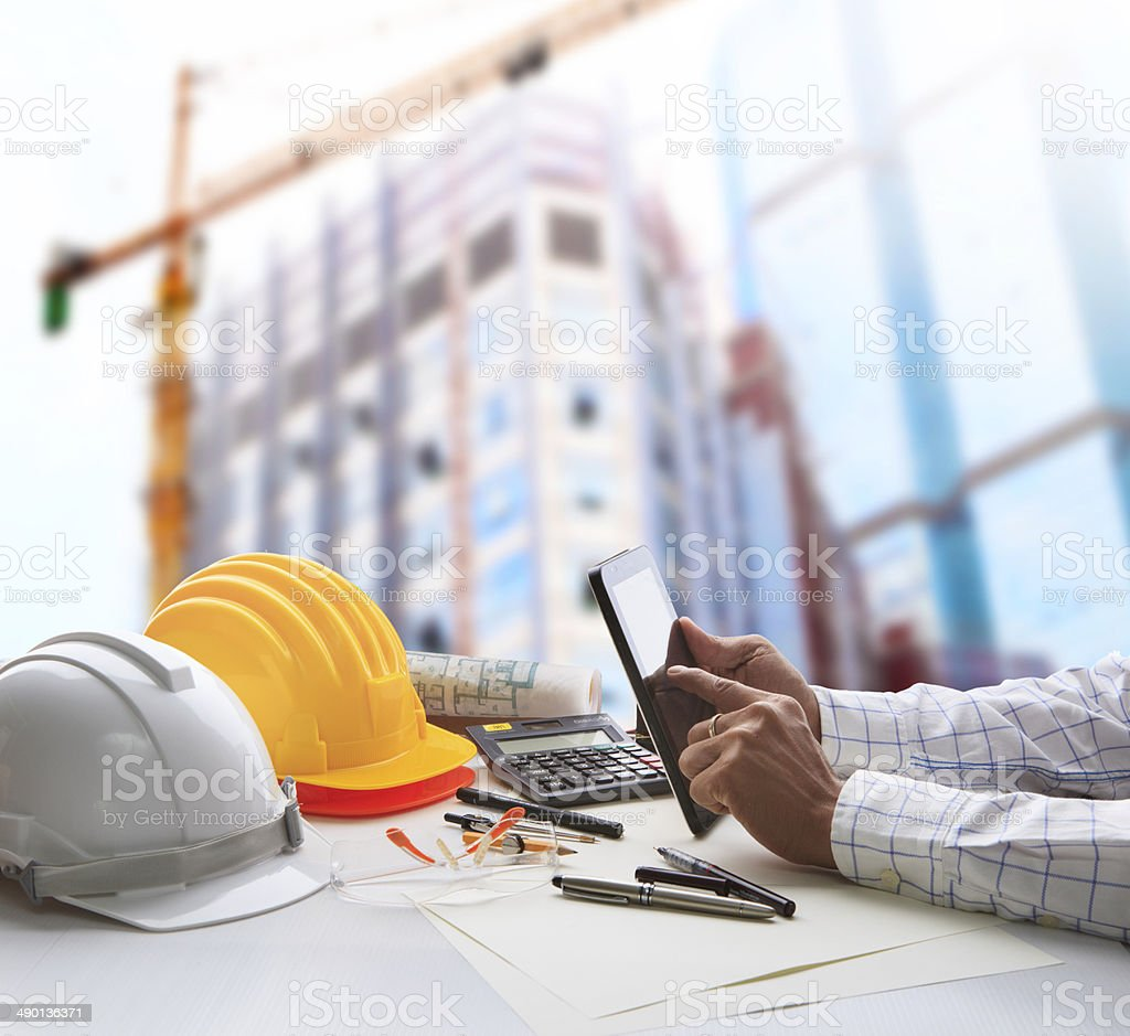 engineer working on table with building construction background stock photo