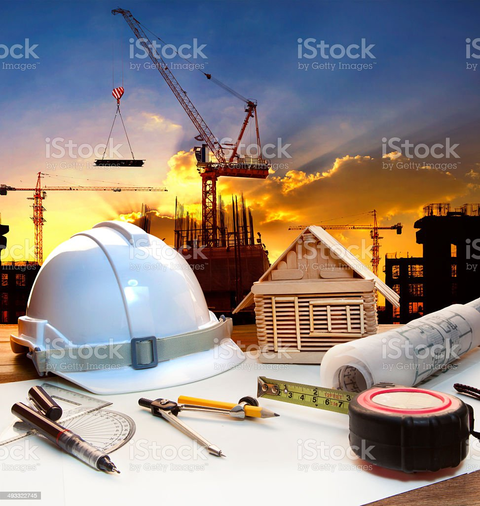 engineer working table against building construction stock photo