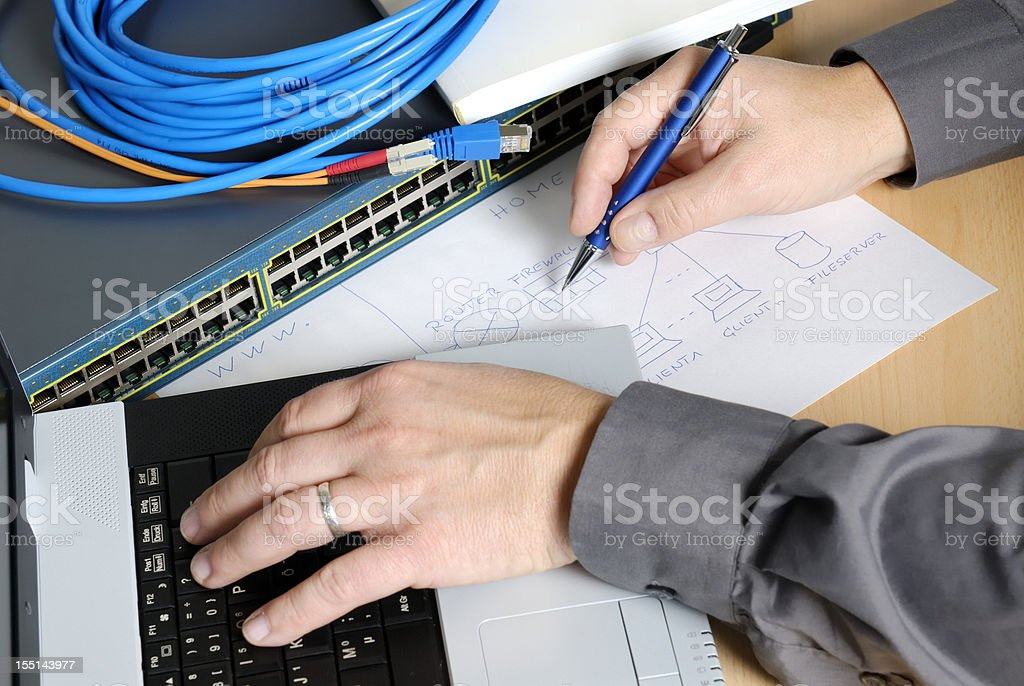 Engineer working with a laptop and paper stock photo