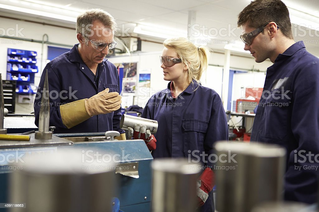 Engineer Working With Apprentices On Factory Floor royalty-free stock photo
