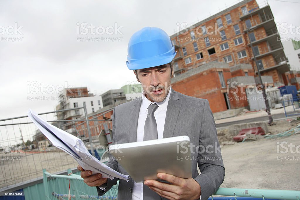 Engineer working with plan and  digital tablet in construction site royalty-free stock photo
