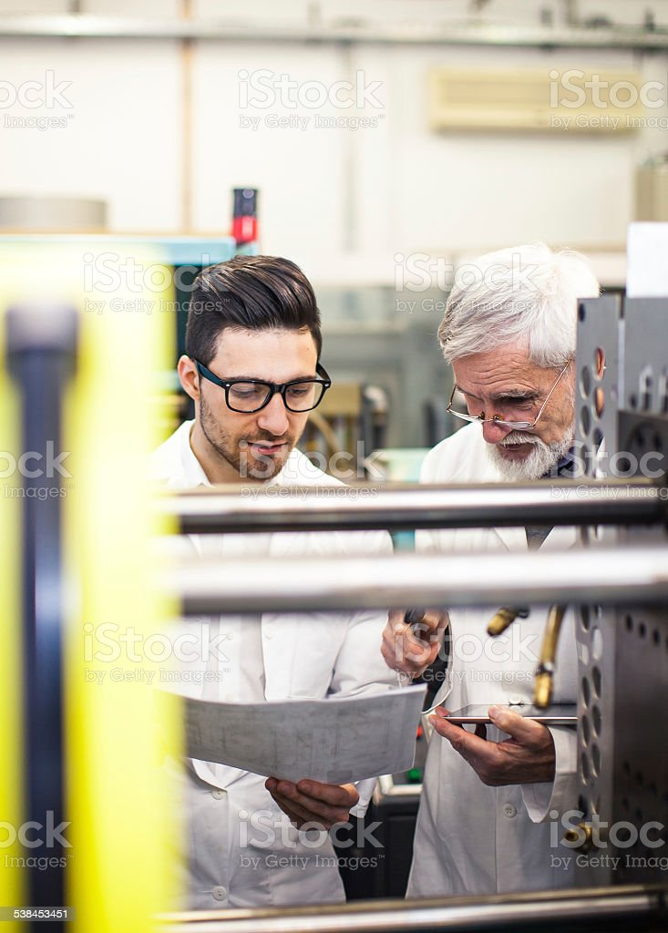 Engineer working with the machine in the factory stock photo