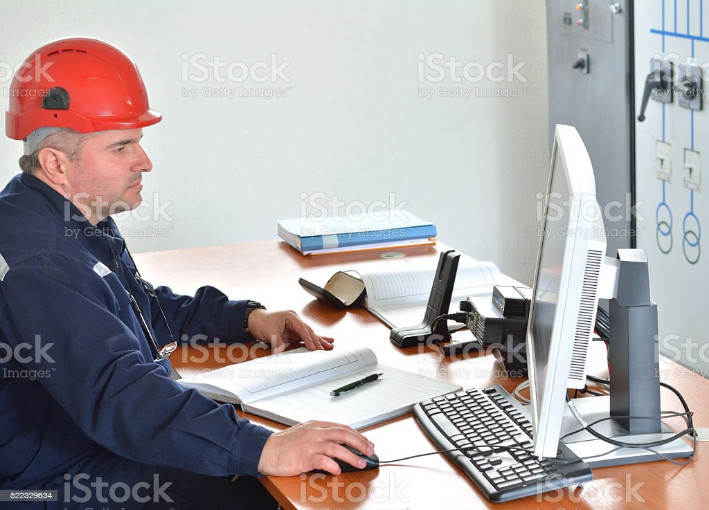 Engineer Works at Desk in Power Plant stock photo