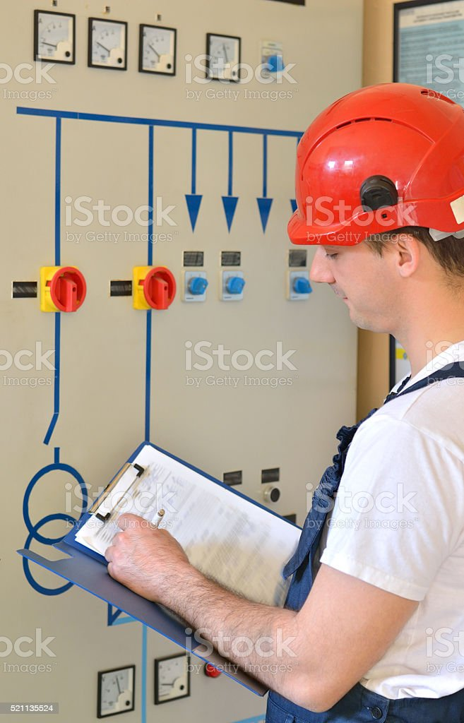 Engineer Writing at File on Control Panel in Electrical Room stock photo