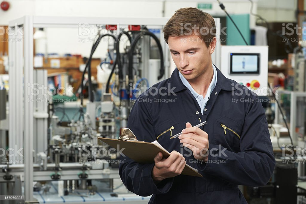Engineer Writing On Clipboard In Factory stock photo